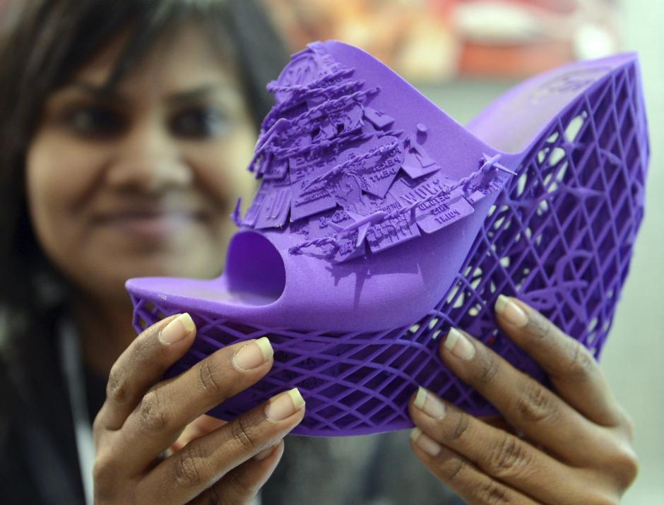 Una azafata muestra un zueco fabricado con una impresora en 3D durante la Feria CES de electrónica en Las Vegas (EE.UU.). Esta nueva técnica permite crear cualquier objeto con la ventaja de que se reducen notablemente los costes. (Foto: EFE/Britta Pedersen)