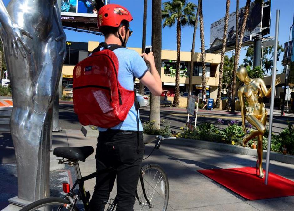 """Un ciclista fotografía un trabajo artístico llamado """"Back-up plan"""" del artista local Plastic Jesus en Hollywood (EFE/Paul Buck)"""