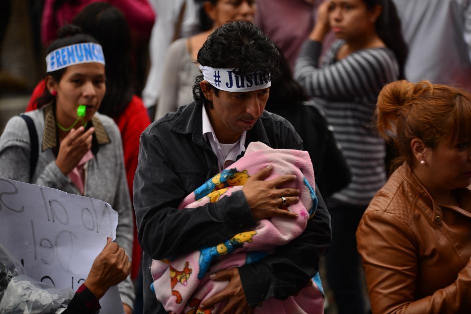 En medio de los gritos y lluvia de la Marcha Pacífica, este padre busca resguardo para su bebé. (Foto: Wilder López/Soy502)