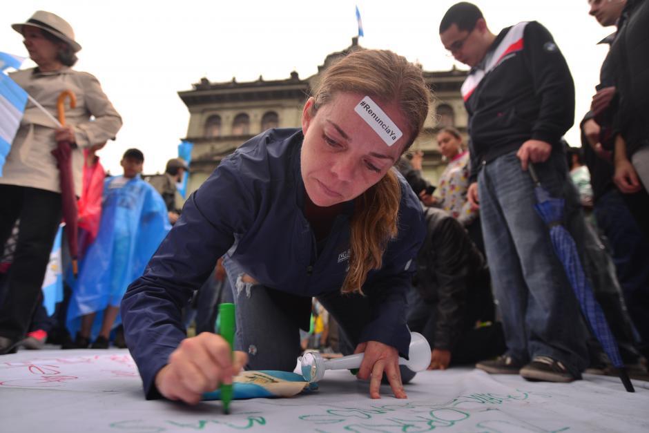 Muchos guatemaltecos escribieron sus demandas al presidente Otto Pérez Molina en la manta gigante frente al Palacio Nacional de la Cultura. (Foto: Wilder López/Soy502)