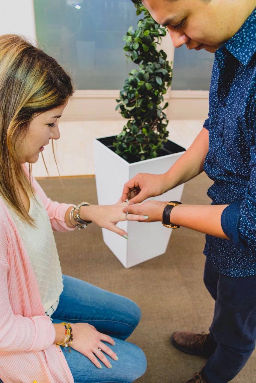 El joven le pone al anillo de compromiso. (Foto: Santos Fotografía/Facebook)