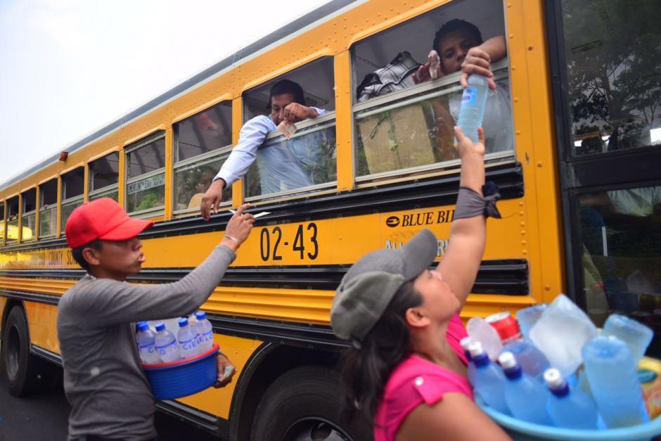 Los vendedores ambulantes aprovechan para vender agua pura a los viajeros. (Foto: Jesús Alfonso/Soy502)