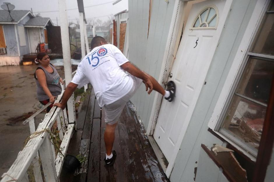 Un hombre trata de tirar la puerta de su residencia, después del paso de Harvey. (Foto: AFP).