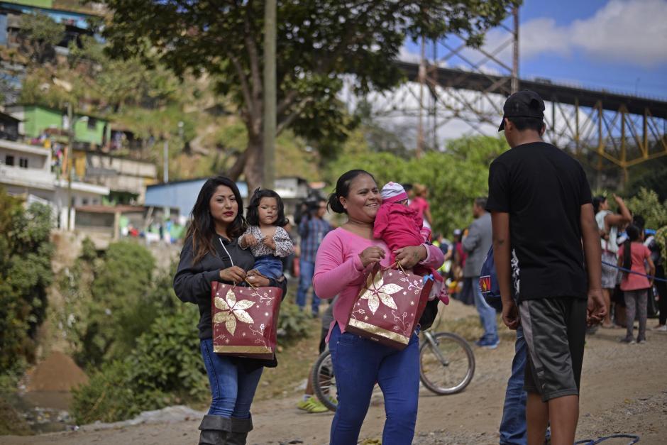 Chacón, con la ayuda de otros bomberos y su familia, se encarga de envolver los regalos. (Foto: Wilder López/Soy502)