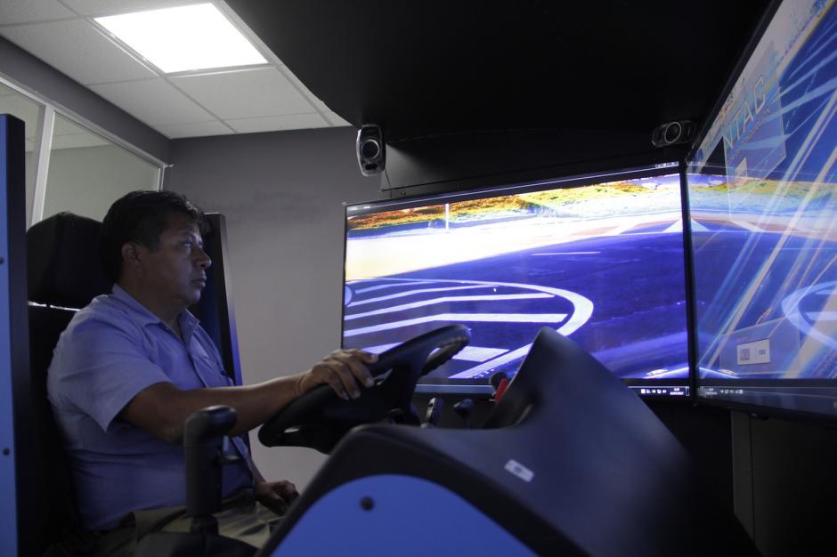 El piloto se sienta frente a un panel de pantallas que simulan una ruta. (Foto: Fredy Hernández/Soy502)
