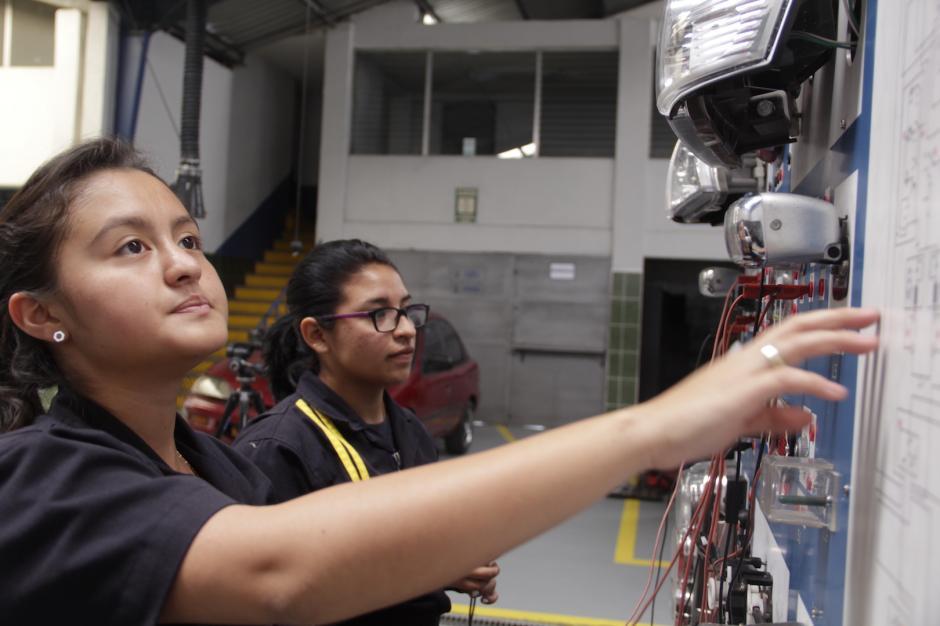 Esther y Lisbeth aprenden sobre la instalación eléctrica de un vehículo. (Foto: Fredy Hernández/Soy502)