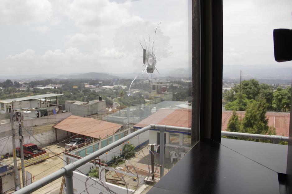 La ventana de su oficina se encuentra perforada por un disparo hecho desde la calle. (Foto: Fredy Hernández/Soy502)