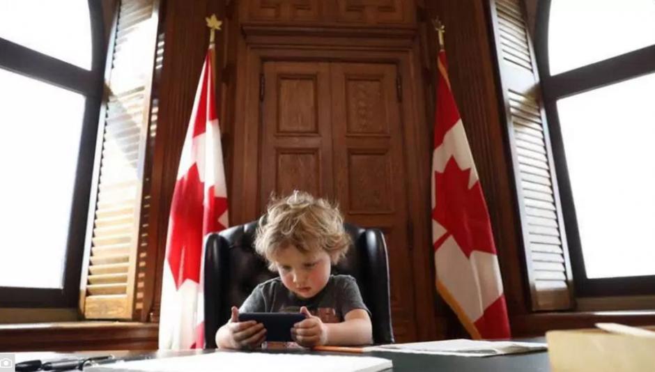 Cómodamente sentado mira el teléfono de su padre. (Foto: facebook)