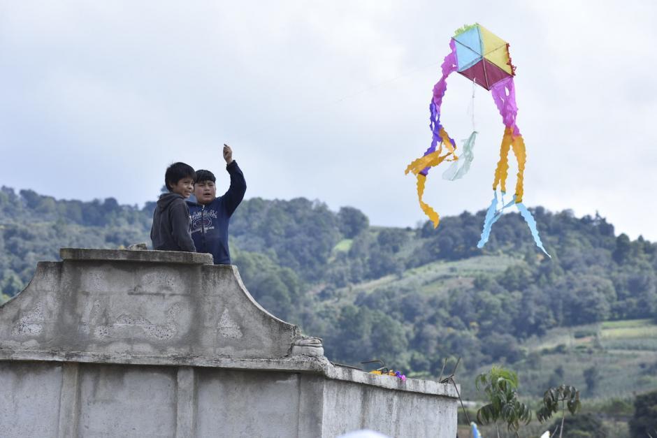 Un niño trata de elevar un barrilete sobre una tumba. (Foto: Cecilia Vicente/Nuestro Diario)
