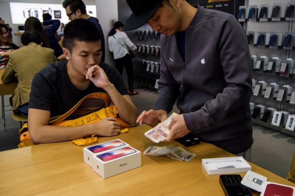 Un cajero cuenta el dinero de un comprador de dos iPhone X. (Foto: AFP)