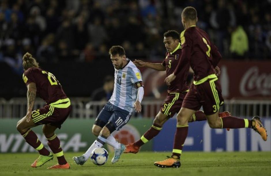 Messi solo contra tres jugadores de Venezuela. (Foto: AFP)