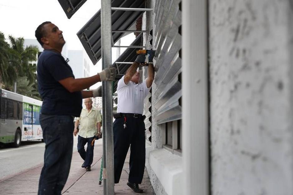 Pobladores refuerzan las ventanas y puertas antes de marcharse. (Foto: AFP)