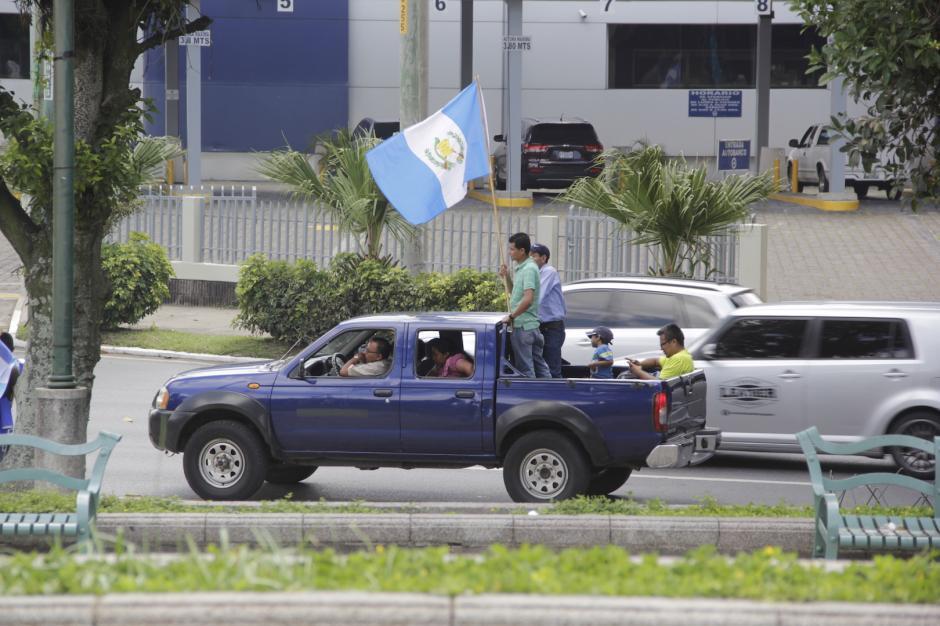Algunos vehículos llevan banderas para unirse a las fiestas patrias. (Foto: Fredy Hernández/Soy502)