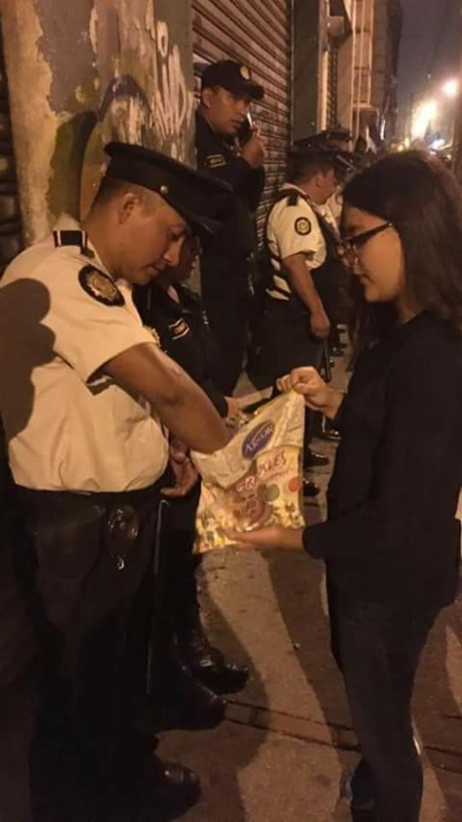 """Una adolescente entrega dulces a los elementos de la PNC que se encuentran alrededor del Congreso. (Foto: Facebook/Usac Es Pueblo """"Oficial"""")"""