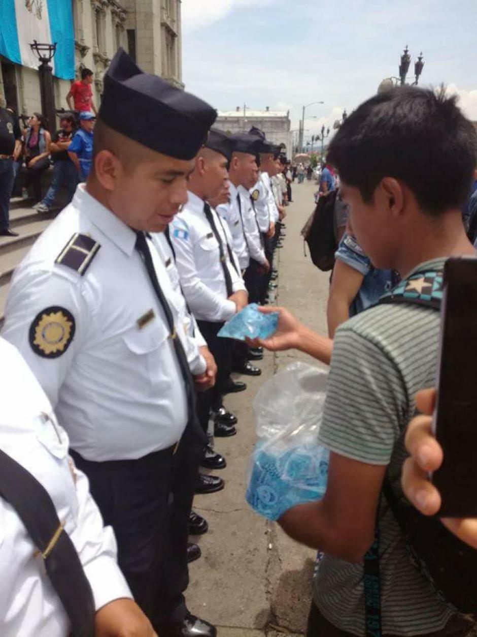 """Un manifestante entregó agua a los agentes de la PNC que resguardaban el Palacio Nacional. (Foto: Facebook/Usac es Pueblo """"Oficial"""")"""