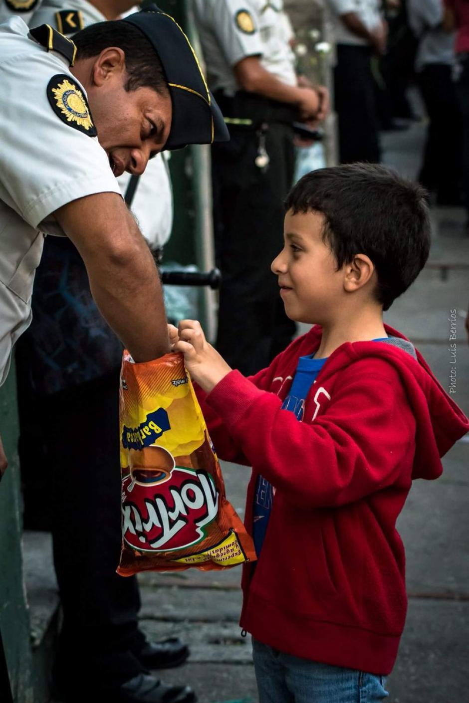 Un niño comparte una bolsa de frituras con un agente de la PNC. (Foto: Luis Berríos)