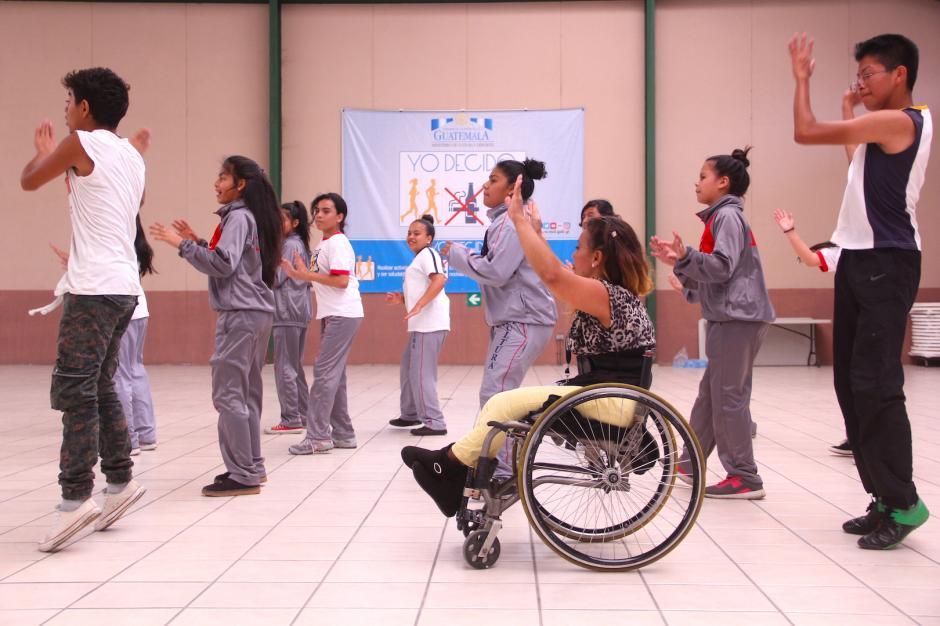La maestra instruye a los estudiantes en un paso de baile latino. (Foto: Fredy Hernández/Soy502)