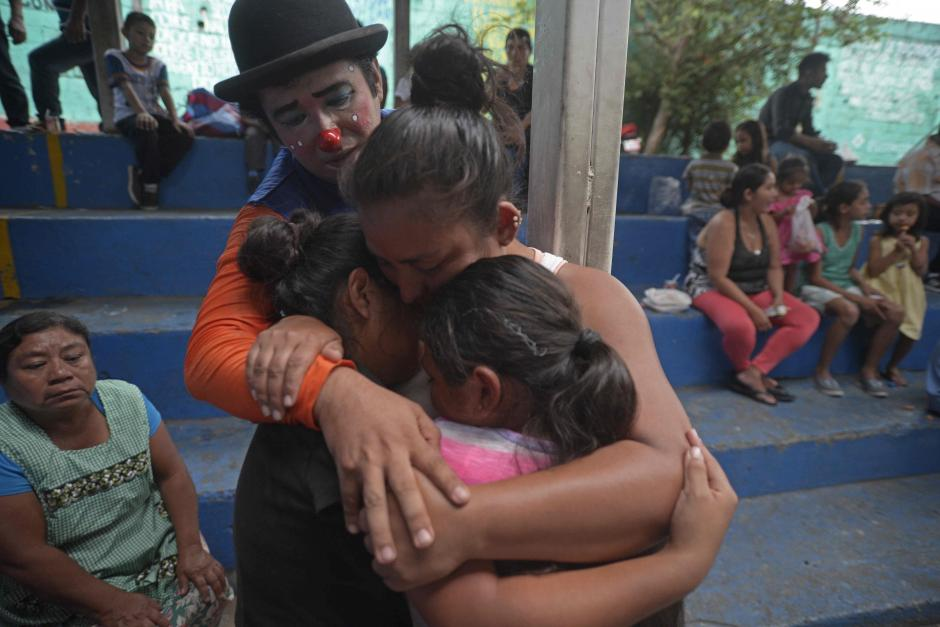 """Martes: """"El Payasito Sonny"""" consuela a una familia en el albergue habilitado en el Instituto Simón Bergaño y Villegas, de Escuintla. (Foto: Wilder López/Soy502)"""