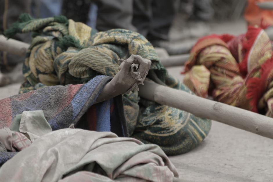 Lunes: El cuerpo de una de las víctimas yace entre otros encontrados bajo el material volcánico. (Fotos: Alejandro Balán/Soy502).