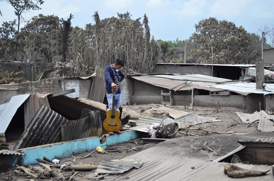 """Jueves: Brayan Rivera sostiene la guitarra de su hermana de 13 años estudiante de la """"Fundación Adentro"""" de Ricardo Arjona. Es lo único que quedó de su casa. (Foto: Lucía Galindo/Soy502)"""