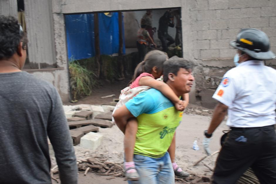 Sin dudar un segundo en arriesgar la vida por su hija, este hombre la toma sobre la espalda y busca ubicarla en un lugar seguro. (Foto: Manuel Cobar/Soy502)