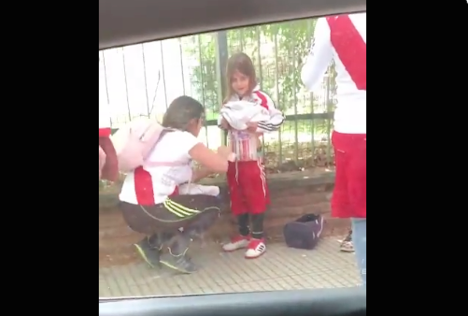 Aficionada de River le coloca bengalas a una niña para ingresar al Monumental. (Foto: Captura de video)