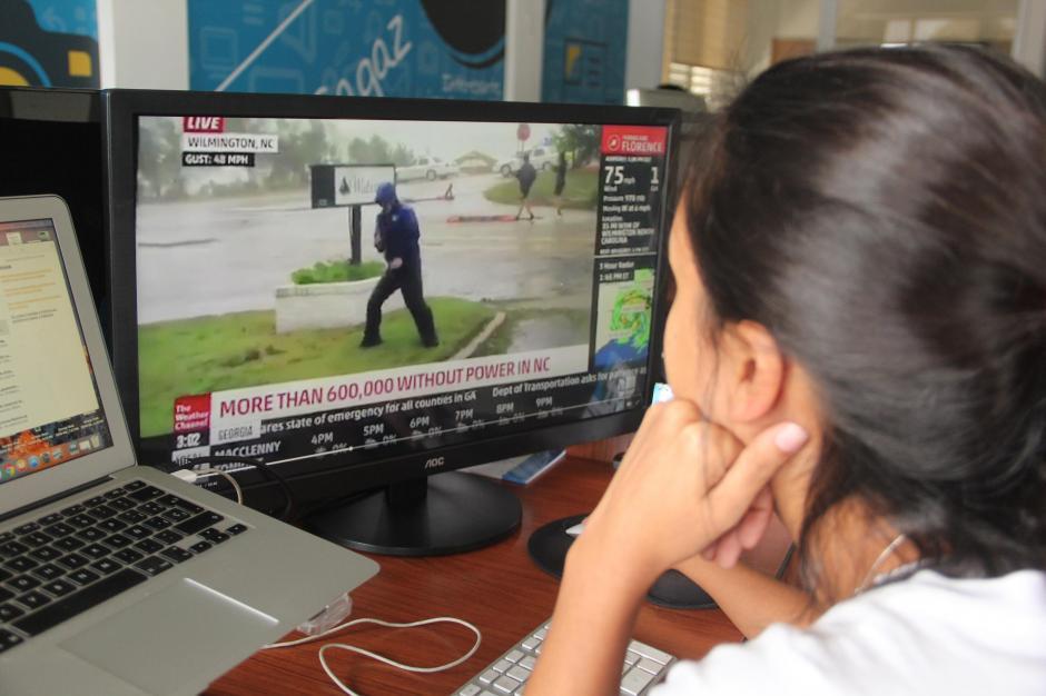 Peatones caminan por la calle mientras un reportero lucha contra 'Florence'