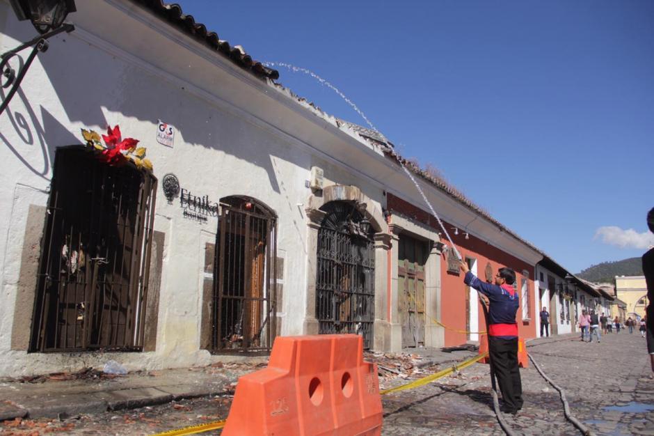 Empleados de los comercios destruidos apagan las brasas aún encendidas. (Foto: Fredy Hernández/Soy502)