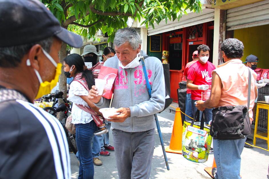 Las personas reciben el almuerzo en punto de las 12:00 en la zona 1. (Foto: Fredy Hernández/Soy502)