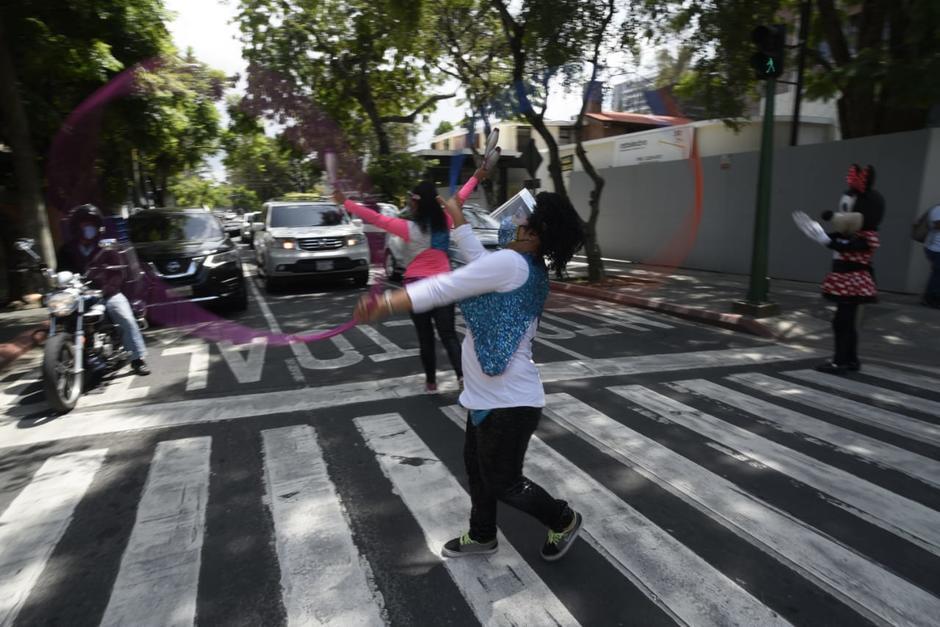 Las payasitas hacen actos de malabarismo a los automovilistas que recorren la zona 10. (Foto: Wilder López/Soy502)