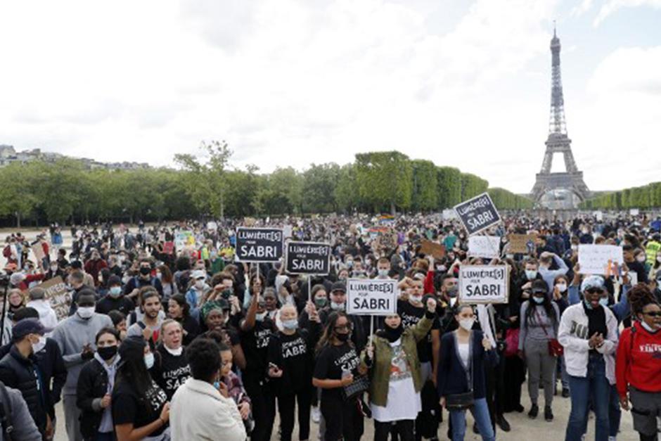 Cientos de personas sostienen pancartas frente a la Torre Eiffel, en París (Fotografía: AFP)