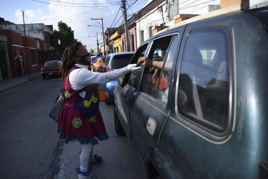 Una payasita recibe un aporte de un automovilista. (Foto: Johan Ordóñez/AFP)