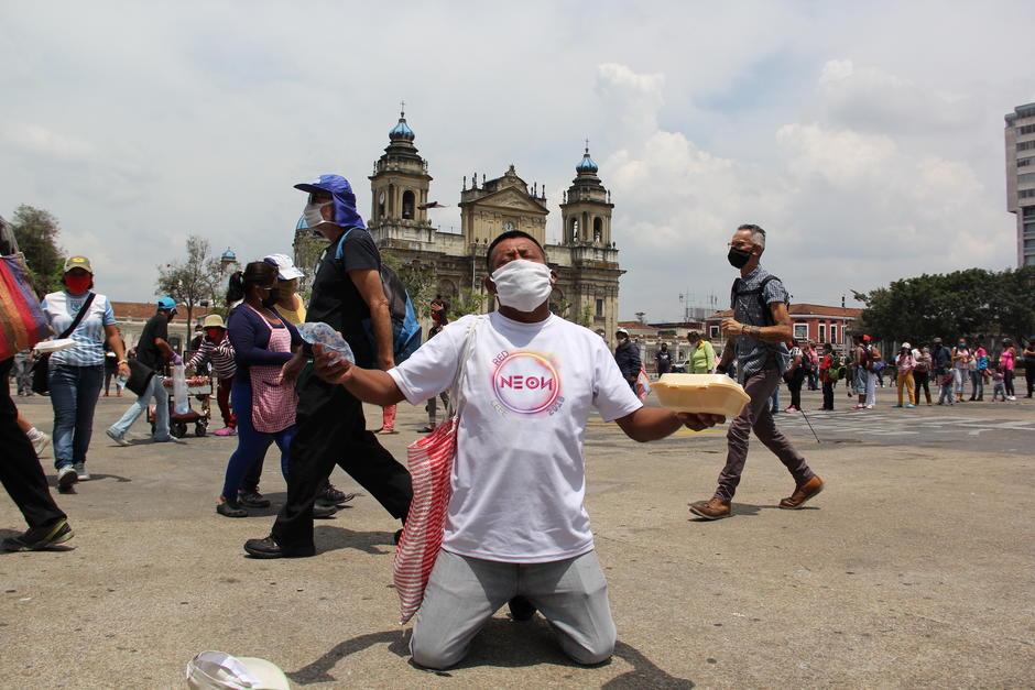 Un hombre se arrodilla tras recibir sus alimentos por parte de la Olla Comunitaria en la Plaza de la Constitución. (Foto: Fredy Hernández/Soy502)
