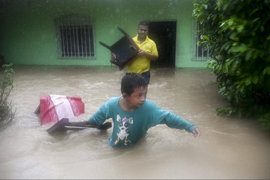 Un niño sale de su casa y ayuda a cargar muebles tras la inundación. (Foto: AFP)