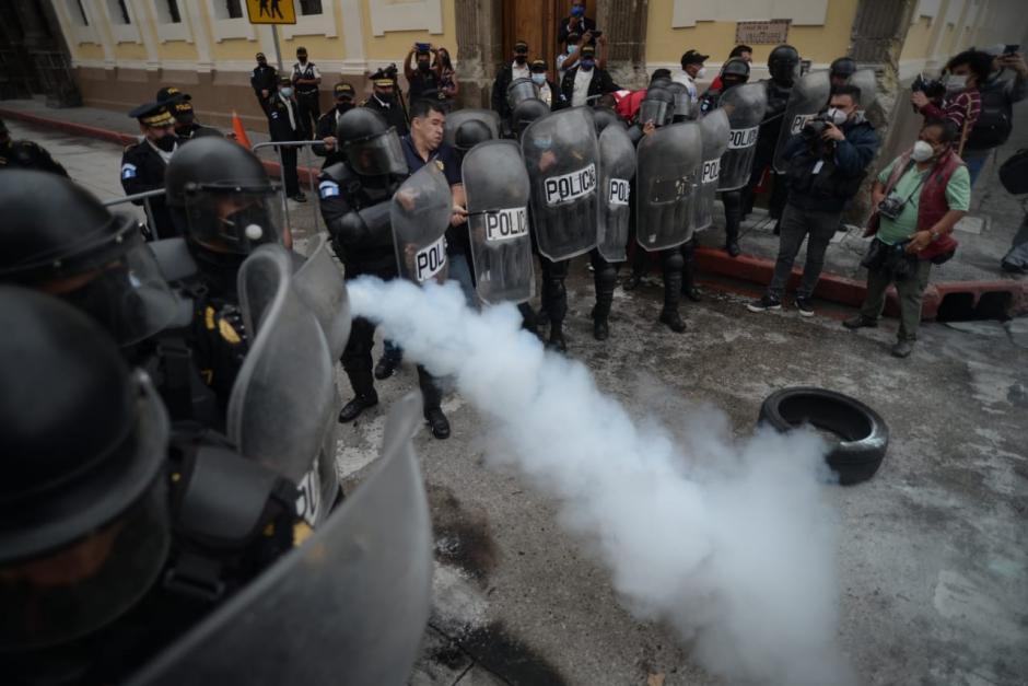 Un empleado del Congreso, resguardado por la PNC, apaga con un extintor las llantas. (Foto: Wilder López/Soy502)