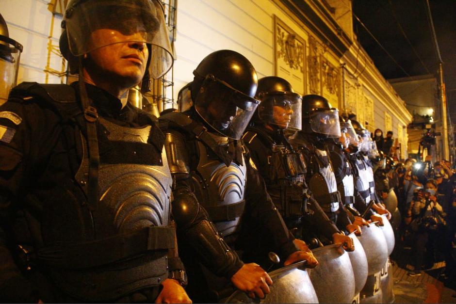 Los agentes antidisturbios bajan sus escudos durante la manifestación. (Foto: Alexis Batres/Soy502)