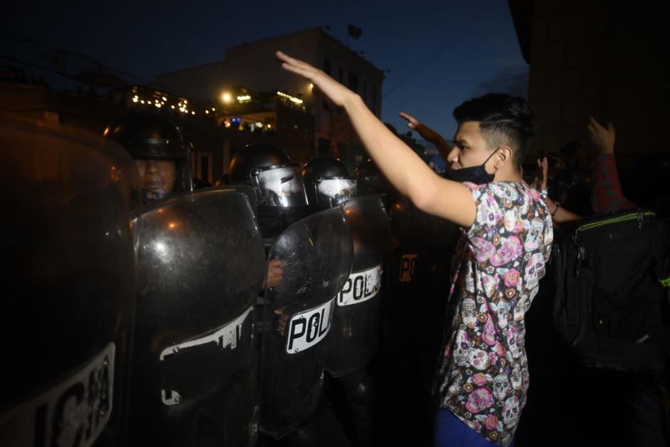 Un joven trata de calmar a los agentes y señala que los jóvenes provocadores son infiltrados. (Foto: Wilder López/Soy502)