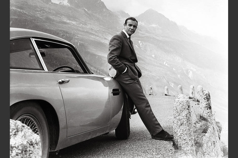 En su papel de James Bond, sobre su clásico Aston Martin