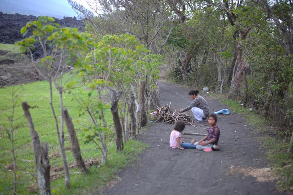 Una mujer y sus hijas llegan cerca de la lava petrificada para conseguir leña de los árboles que se quemaron o se secaron con la incandescencia. (Foto: Wilder López/Soy502)