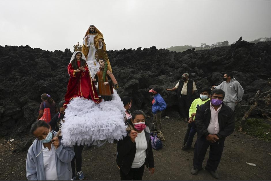 Los pobladores cargan imágenes religiosas para pedir que el volcán Pacaya pueda volver a la calma. (Foto: Johan Ordóñez/AFP)