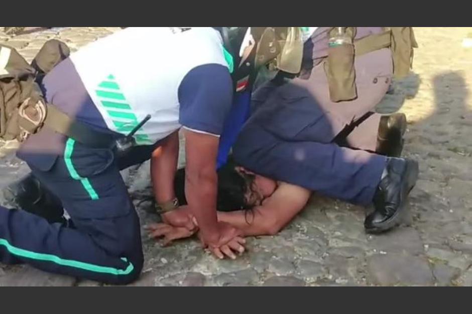 Policías Municipales de Antigua Guatemala, Sacatepéquez, toman por la fuerza a persona que caminaba desnudo por la Calle de las Ánimas. (Foto: Captura de Pantalla)