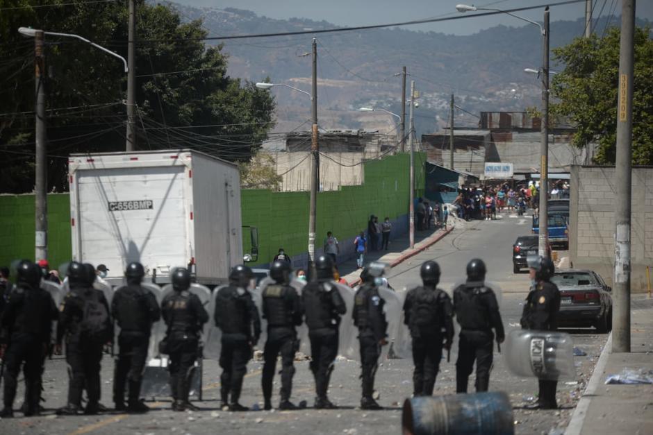 Fuerzas Especiales de la PNC forma una valla en medio de los invasores y los vecinos de Nimajuyó. (Foto: Wilder López/Soy502)