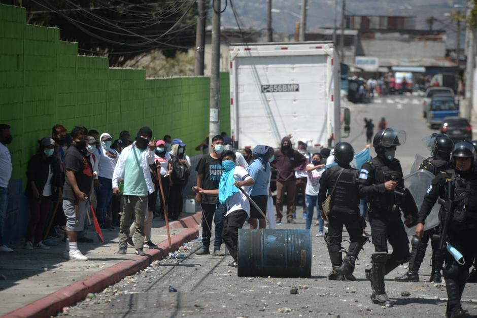 Momento en el que uno de los invasores lanza una piedra contra los vecinos de Nimajuyú, zona 21. (Foto: Wilder López/Soy502)