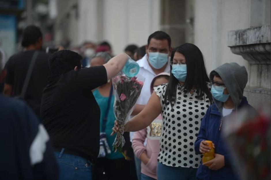 Guatemaltecos hacen fila en las afueras del templo para depositar sus flores en el altar. (Foto: Wilder López/Soy502)