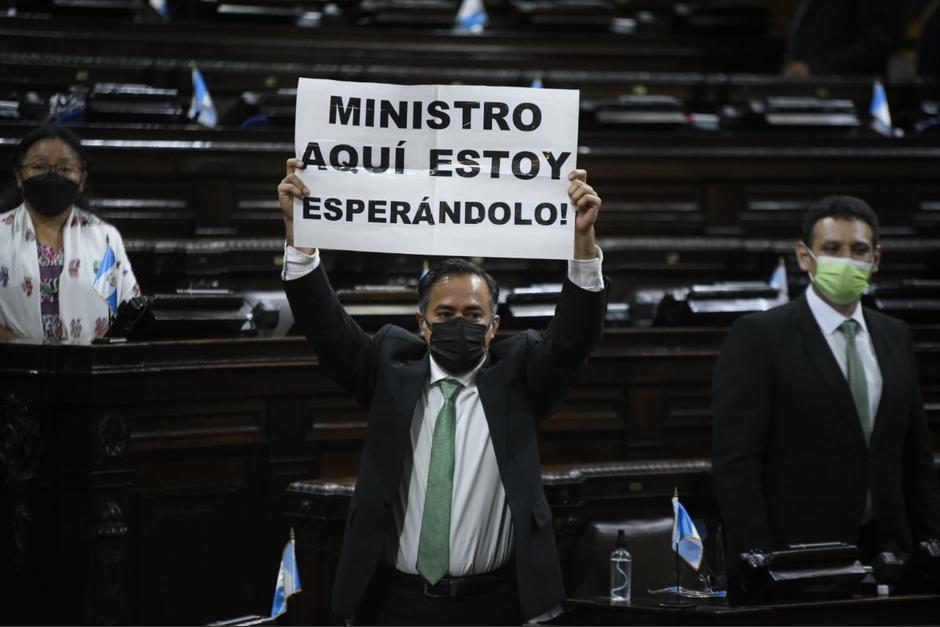 El diputado de la UNE, Jairo Flores, sostiene un cartel donde reclama la presencia del ministro de Energía y Minas, Alberto Pimentel, a la interpelación. (Foto: Wilder López/Soy502)
