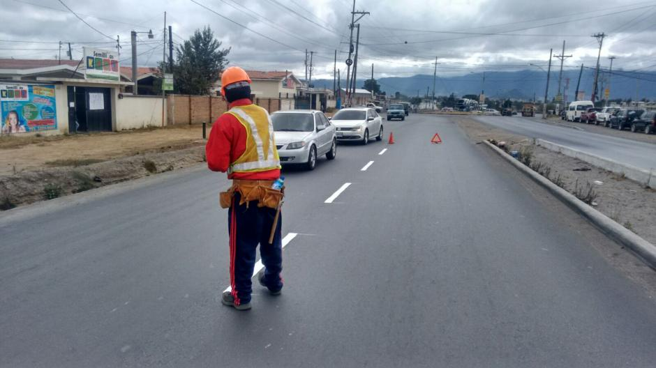 Los dos hombres se turnan para pintar y solicitar colaboración a los automovilistas para la compra de los materiales necesarios para su trabajo. (Foto: Carlos González/Stereo100Xela)