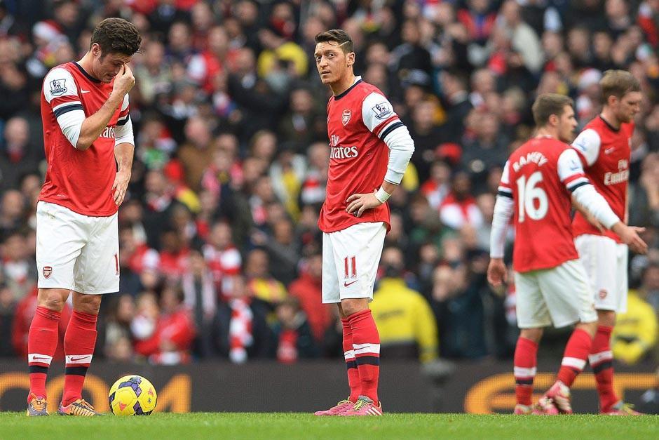 Olivier Giroud y Mesut Ozil se lamentan tras el segundo gol del Manchester City. (Fotos: Peter Powell/EFE)
