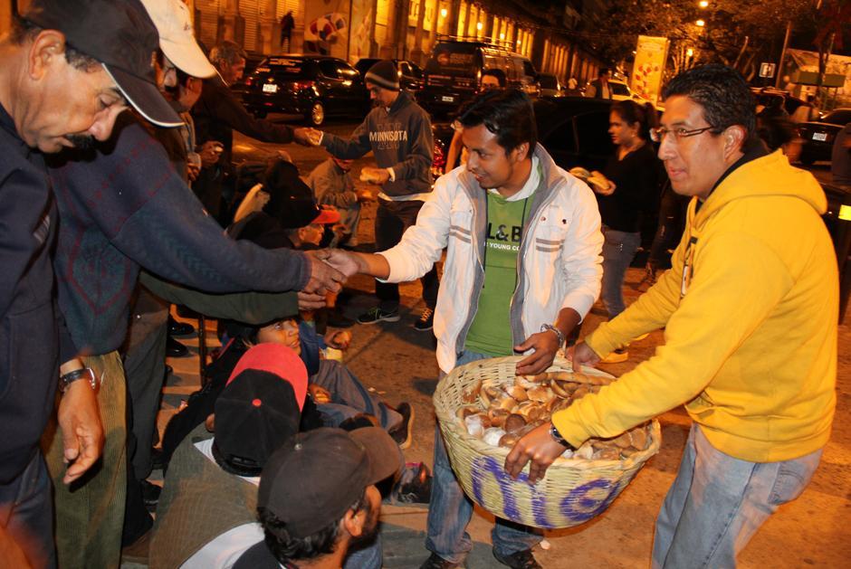 A las 5:30 am los voluntarios de Panito reparten pan a la gente que vive en las calles frente a la Catedral Metropolitana. (Foto: Luis Barrios/Soy502)