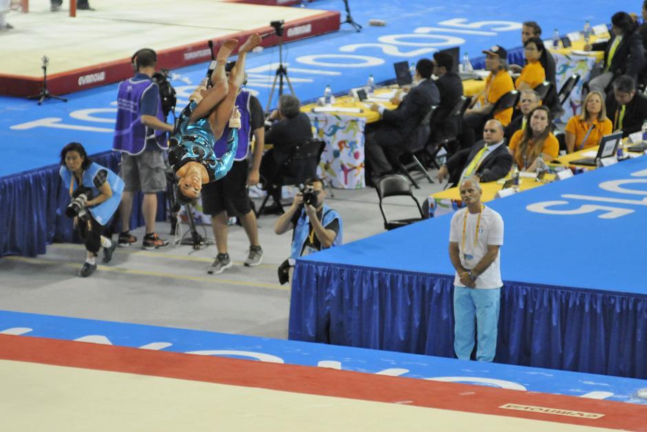 La gimnasta realiza su rutina de piso mientras atrás la ve su entrenador Adrían Boboc