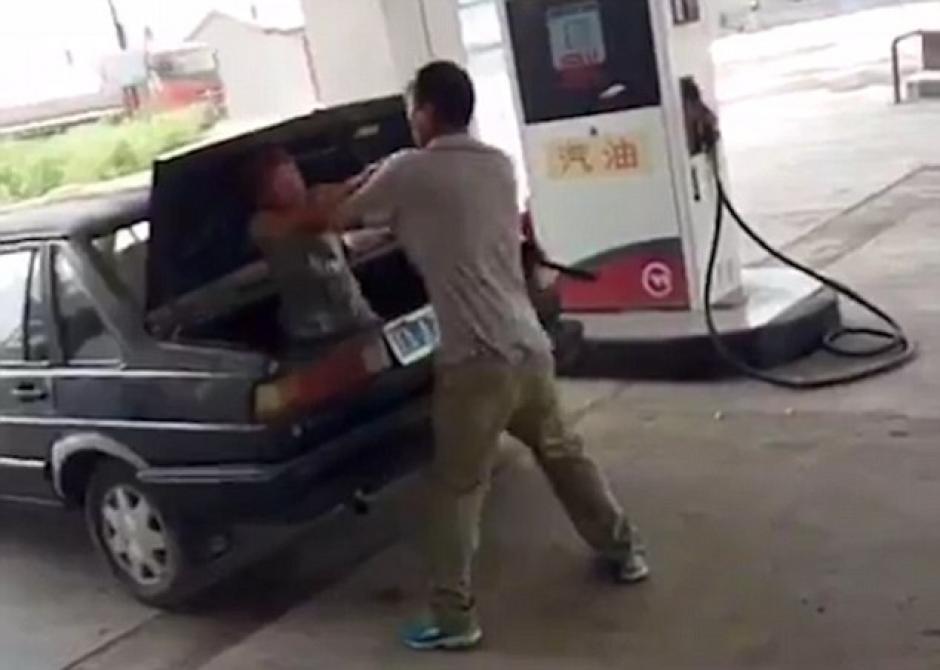 El hombre furioso mete a su mujer en el maletero de un auto. (Foto: Dailymail)